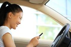 妇女司机用途在汽车的手机 免版税库存图片