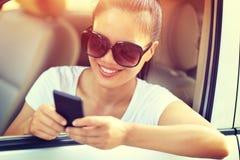 妇女司机用途在汽车的手机 库存照片