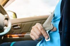 妇女司机紧固汽车安全安全带,运输和 免版税库存照片