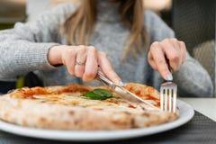 妇女吃与刀子并且分叉一比萨马尔盖里塔用无盐干酪蕃茄和蓬蒿 从wood-burning的那不勒斯的比萨 库存图片