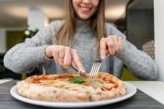 妇女吃与刀子并且分叉一比萨马尔盖里塔用无盐干酪蕃茄和蓬蒿 从wood-burning的那不勒斯的比萨 免版税图库摄影