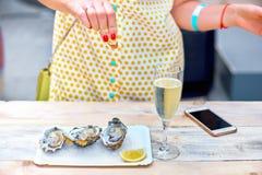 妇女吃在板材的新鲜的牡蛎 图库摄影