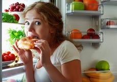 妇女吃夜女用披肩冰箱 免版税库存照片
