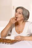 妇女吃巧克力糖 免版税库存照片