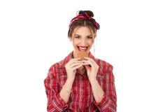 妇女吃曲奇饼微笑愉快 图库摄影