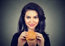 妇女吃汉堡微笑 美好的女性设计 免版税库存图片