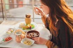 妇女吃从丸子和瓦器kebab的土耳其食物 免版税库存照片