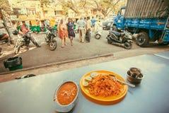 妇女向在街道daal咖啡馆与印地安食物biryani和的扁豆的晚餐求助 库存照片