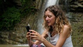 妇女听到与耳机的音乐并且使用智能手机反对大瀑布 股票录像