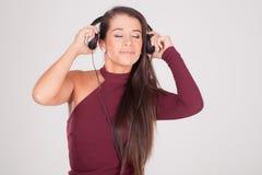 妇女听到在耳机的音乐 库存照片