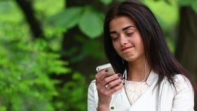 妇女听到从一个巧妙的电话的音乐的有耳机的在公园,使用有耳机的美丽的妇女智能手机 股票视频