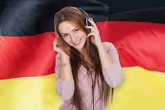 妇女听的德国学习的audiobook 免版税库存照片