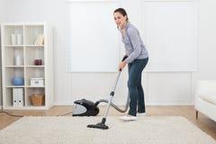 妇女吸尘的地毯在家 免版税库存照片