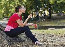 妇女吹的泡影在公园 库存图片