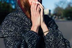 妇女吹的鼻子在公园 库存图片