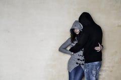 妇女和一个人穿戴了与灰色和黑衣裳,两条佩带的蓝色牛仔裤,拥抱,倾斜在织地不很细墙壁 库存照片