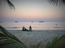 妇女和一个人观看在美丽的热带海滩和海洋水的日落焕发 库存图片