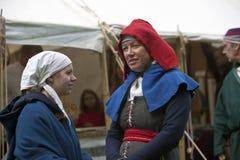 妇女和一个女孩中世纪服装谈话的。 免版税库存图片
