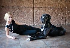 妇女和一条狗在地板上 库存图片