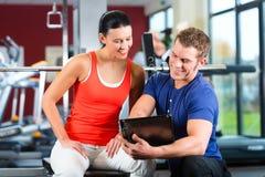 妇女和个人教练员在健身健身房 库存照片