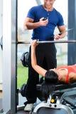 妇女和个人教练员在健身房 库存图片