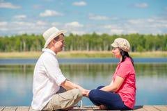 妇女和人一个木码头的在湖附近 库存图片