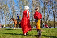妇女和人中世纪服装的谈话与中世纪御马者在圣乔治的国际骑士节日比赛 库存照片