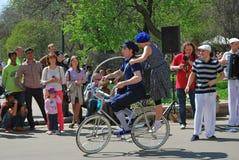 妇女和人乘驾一自行车 免版税库存图片