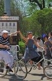 妇女和人握手的乘驾自行车 库存照片