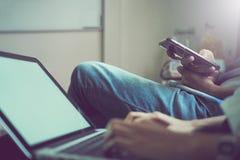 妇女和人是朋友 使用电话和计算机科技骗局 图库摄影