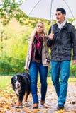 妇女和人有与狗的步行在秋天雨中 免版税库存图片
