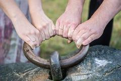 妇女和人有婚戒的` s胳膊拉扯一个大金属圆环 免版税库存照片