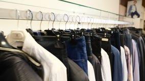 妇女和人的射击的衣裳 衣物的挂衣架在户内商店 被射击的衣物的关闭在比分,长行 股票视频