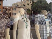 妇女和人站立在店面窗口里的时装模特形象 库存照片