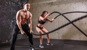 妇女和人结合训练一起做作战的绳索锻炼 库存图片