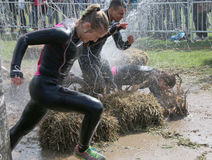 妇女和人赛跑,一名妇女在泥下落了 库存照片