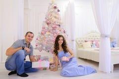 妇女和人递圣诞节礼物它的在宽敞bedro的一半 库存照片
