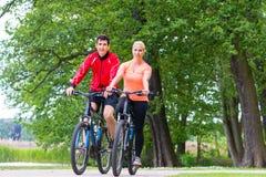 妇女和人登山车的在森林 免版税图库摄影