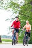 妇女和人登山车的在森林 库存照片
