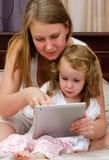 妇女和使用片剂个人计算机的小女孩 免版税库存图片