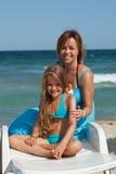 妇女和使用遮光剂奶油的小女孩 免版税库存图片