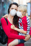 妇女和儿子佩带的面罩 免版税库存图片