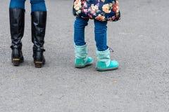 妇女和儿童佩带的起动身分-图象的腿在柏油路的 库存图片