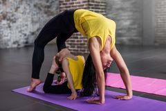 妇女和儿童女孩实践的瑜伽一起在家,做眼镜王蛇的成人站立在桥梁姿势的和孩子 免版税库存照片