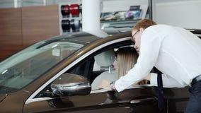 妇女和售货员咨询缓慢的射击在汽车商店 股票视频