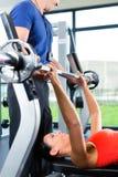 妇女和在健身房的私有培训人 免版税库存图片