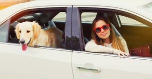 妇女和坐在汽车的金毛猎犬狗看窗口 免版税库存照片