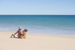妇女和坐在热带海滩的爱犬 免版税库存照片