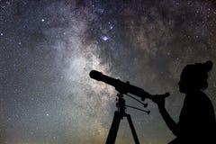 妇女和夜空 观看有望远镜的星妇女 免版税库存图片