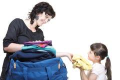 妇女和女儿手充分填入了衣裳和书包 图库摄影